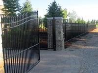 20ft Wide Iron Double Gate (two 10ft halves) in a 6' Arching to 7' Height Installed with Decorative Columns