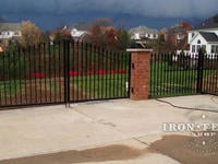 Custom 4ft arching to 5Ft iron driveway gate mounted on brick pillars with matching 4ft iron fence and walk gate (Style #1 - Classic)