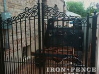 Custom iron driveway gate with decorative scroll top and puppy pickets