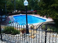 Iron hoop and picket style fence in Traditional grade around a pool (Victorian Hoop)