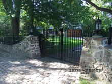 Our Signature Grade Iron Arched Driveway Gate Installed with a Stone Wall
