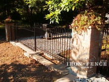 4ft iron hoop and picket style fence stepped for grade between stone columns