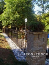 4 foot tall wrought iron hoop and picket style fence between stone pillars