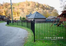 Wrought Iron Fence Angled Around a Curved Road with Straight Panels and Angle Brackets