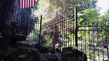 Wrought Iron Fence in Classic Style Installed on a Downhill Incline via Stair-Stepping and Backfilling with Stones