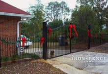 16ft wide iron driveway gate in a 6ft to 7ft height with puppy pickets and matching 4ft tall fence