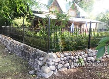 A Custom-Built Wrought Iron Fence with Puppy Pickets and Fleur De Lis Finials on a Rock Wall