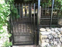 A Custom-Built Iron Gate with Puppy Pickets and Fleur De Lis Finial Tips