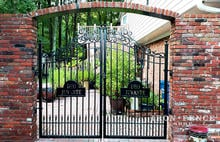 A Custom Iron Gate with Scrollwork and Motto Plate in a Brick Opening