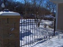 4 foot tall iron hoop and picket fence with stone pillar in winter