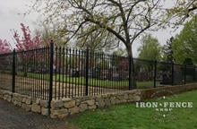 Wrought Iron Fence with Stacked Rock Wall to Handle Grade in the Corner of a Lot