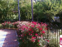 4ft iron hoop and picket fence surrounding a flower bed and patio