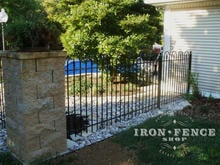 4ft Iron Hoop and Picket style fence surrounding a pool and connecting to stone columns