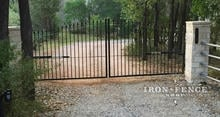 Stronghold Iron Arched Driveway Gate mounted behind Stone Columns