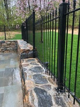An Iron Fence Installed Stair-Step Style Down a Stone Wall Top